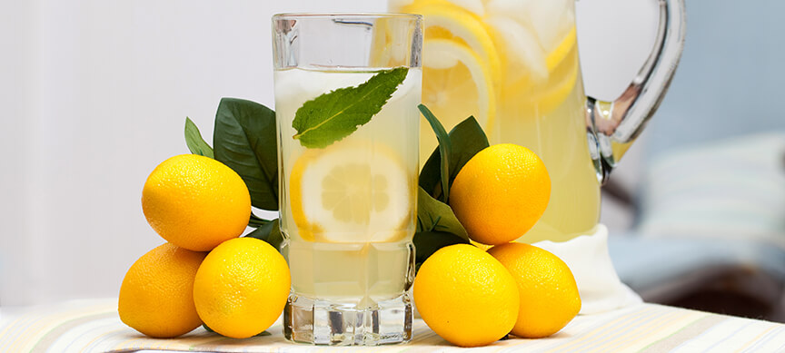 Drinking lemon water - Pitcher and glass of lemon water.